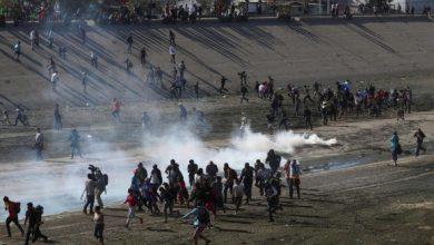 Photo of Migrantes intentan cruzar muro con EEUU y reciben gas lacrimógeno