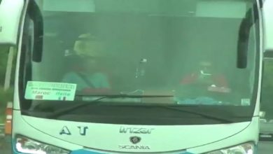 Photo of Captan a un conductor leyendo al volante de un autobús lleno de turistas